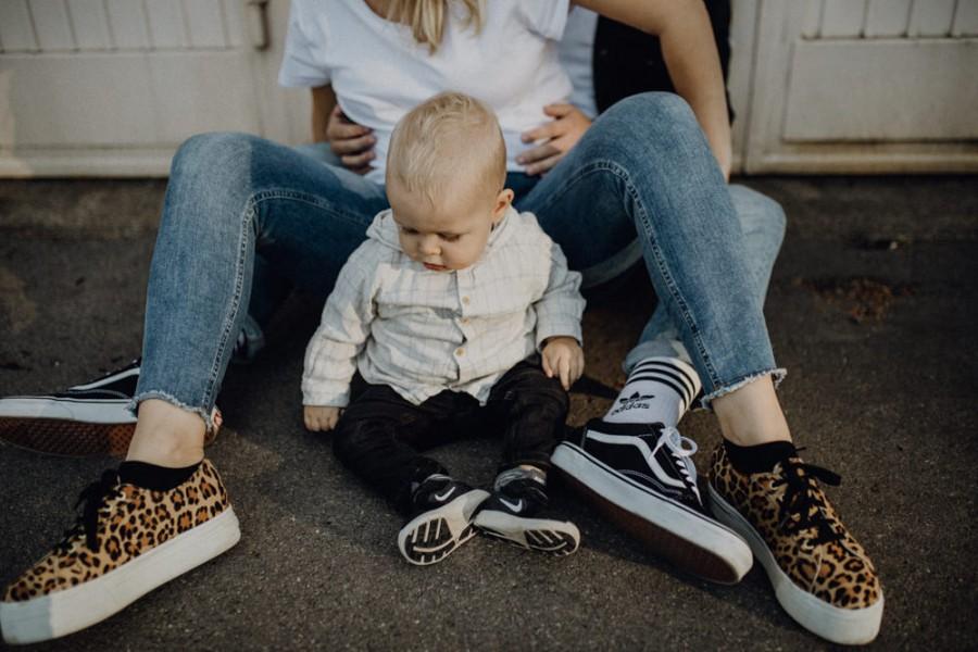 Kind sitzt bei den Eltern, Familienfoto